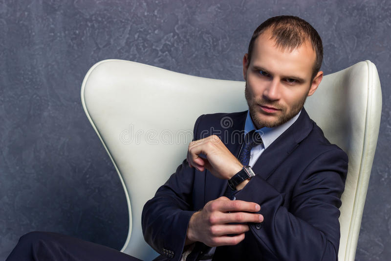 Homens de negócios brutais no terno com o laço que senta-se na cadeira fotografia de stock