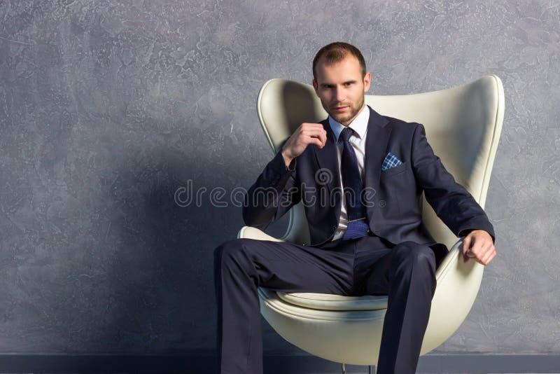 Homens de negócios brutais no terno com o laço que senta-se na cadeira fotos de stock royalty free