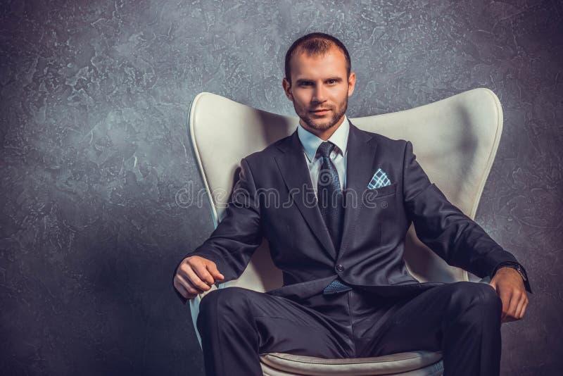 Homens de negócios brutais no terno com o laço que senta-se na cadeira fotografia de stock royalty free