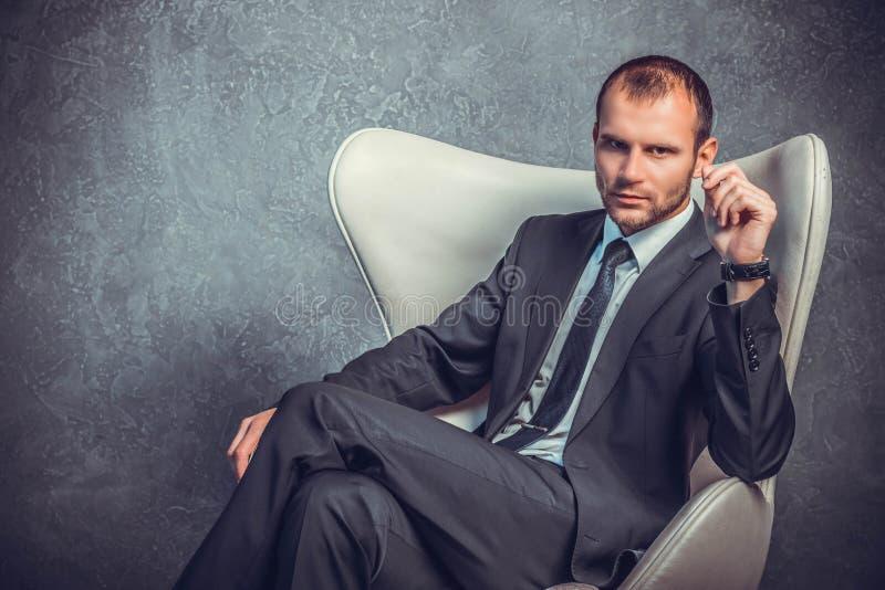 Homens de negócios brutais no terno com o laço que senta-se na cadeira imagem de stock