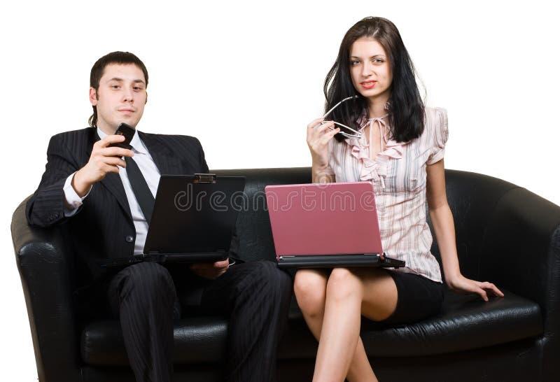 Homens de negócios com os computadores no sofá imagem de stock
