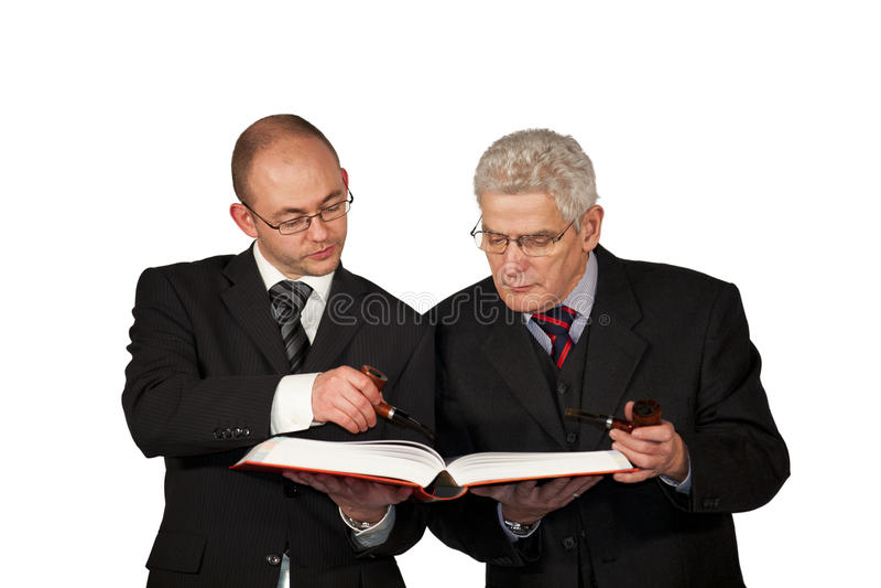 Homens de negócios com tubulações que lêem um livro imagens de stock