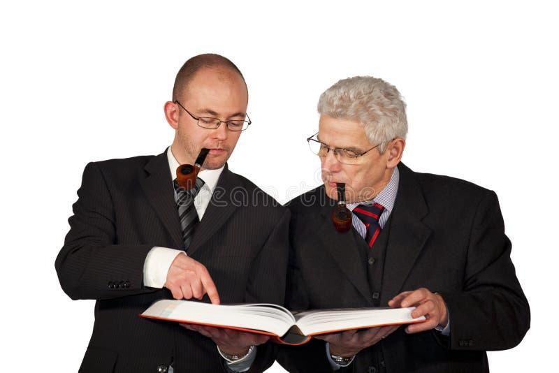 Homens de negócios com tubulações que lêem um livro imagem de stock royalty free
