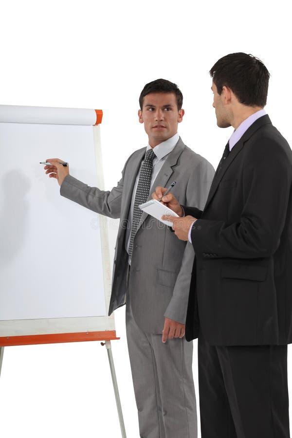 Homens de negócios com um flipchart imagem de stock