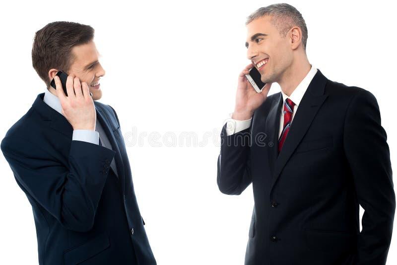 Homens de negócios consideráveis com telefones celulares imagem de stock royalty free