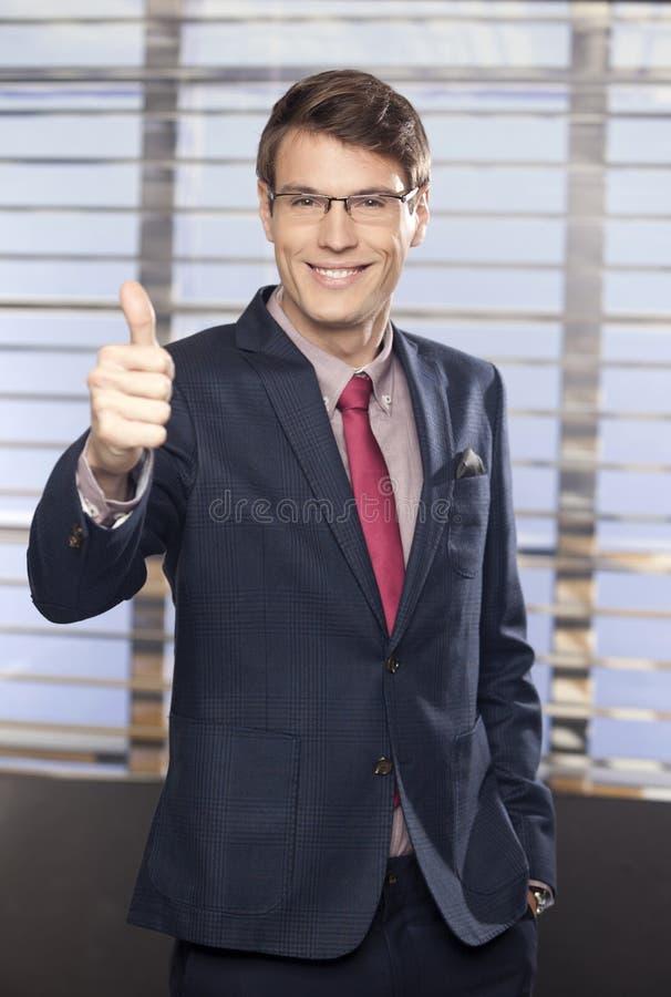 Homens de negócios consideráveis novos que mostram o polegar-acima no escritório fotografia de stock