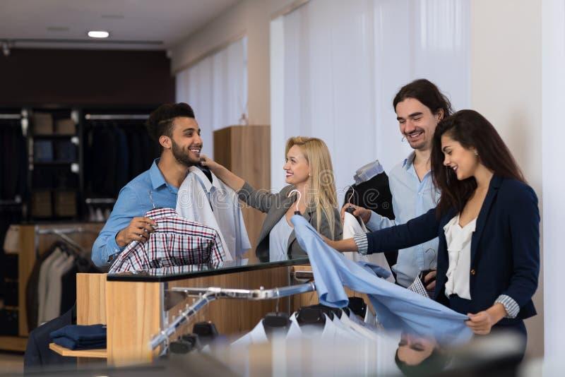 Homens de negócios em camisas da compra do boutique dos ternos do luxo, dois homens de ajuda do vendedor fêmea atrativo para esco foto de stock