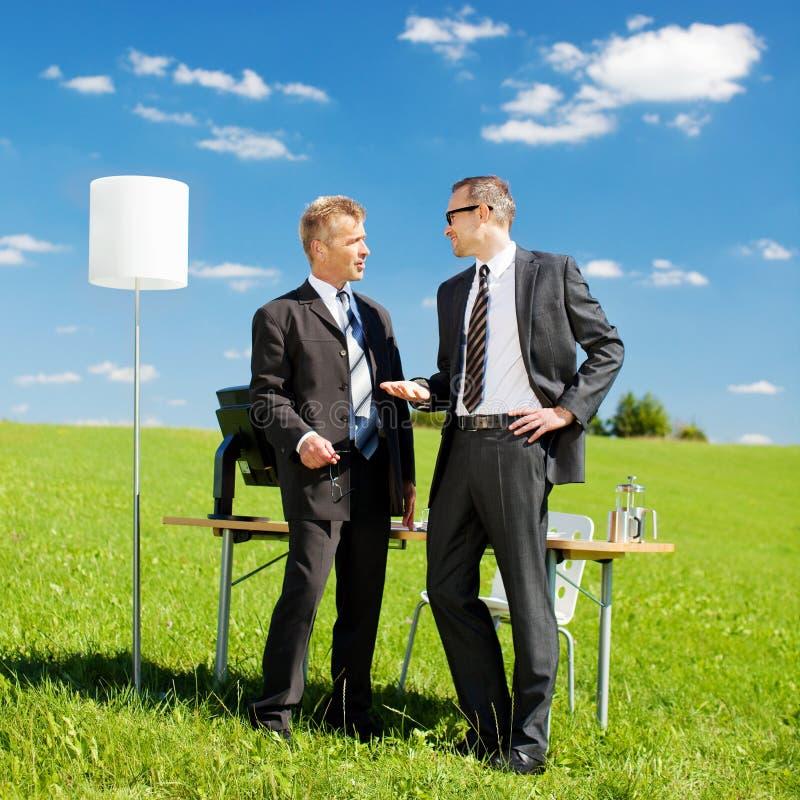 Homens de negócios em uma reunião na natureza fotografia de stock royalty free