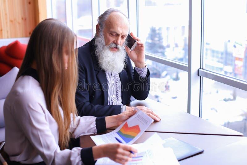 Homens de negócios experientes as tomadas aposentadas chamam o telefone e as partes a fotos de stock royalty free