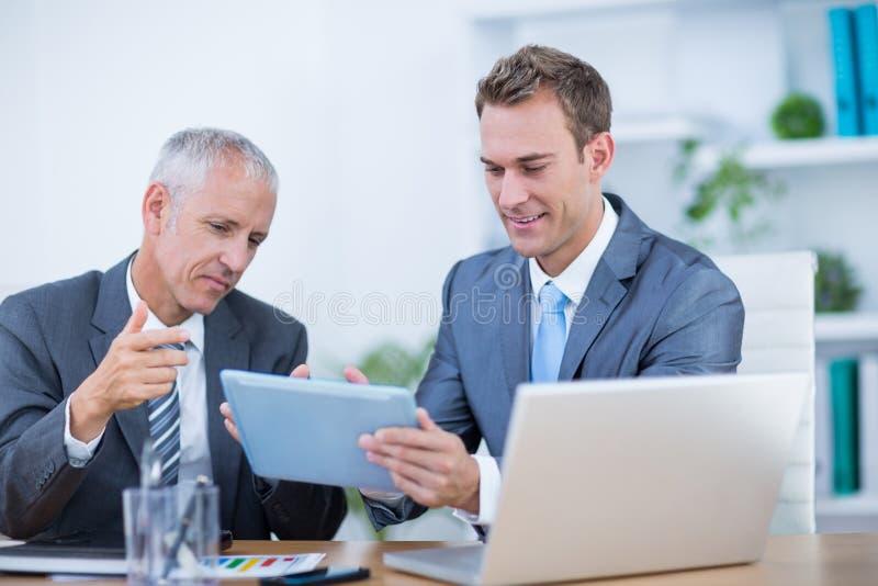 Homens de negócios felizes que trabalham junto na tabuleta digital fotos de stock