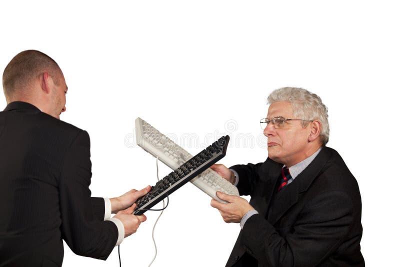 Homens de negócios irritados que lutam com teclados imagens de stock royalty free