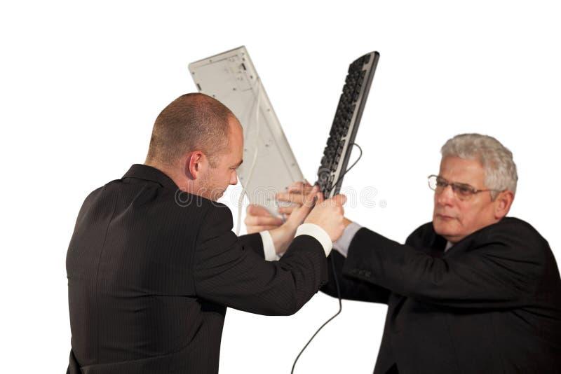 Homens de negócios irritados que lutam com teclados imagem de stock