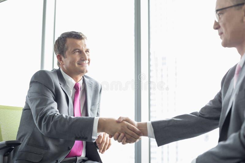 Homens de negócios maduros que agitam as mãos no escritório imagens de stock royalty free