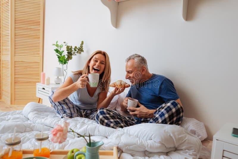 Homens de negócios maduros que apreciam o café da manhã saboroso na cama junto imagens de stock royalty free