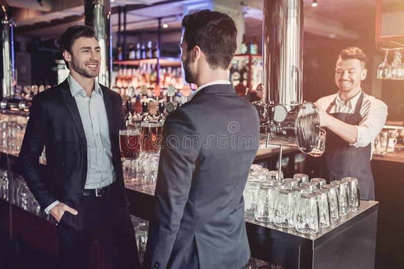 Homens de negócios na barra foto de stock royalty free