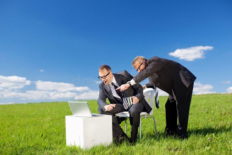 Homens de negócios no prado verde imagem de stock