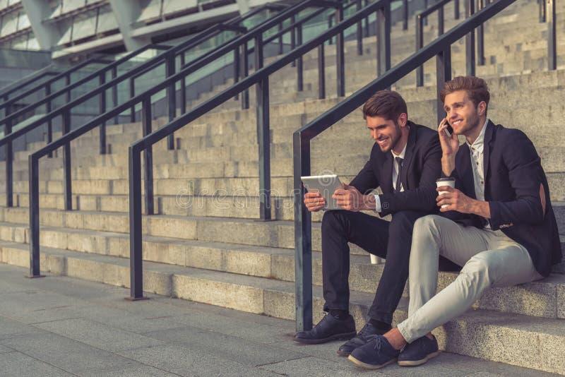 Homens de negócios novos consideráveis com dispositivo fotos de stock royalty free