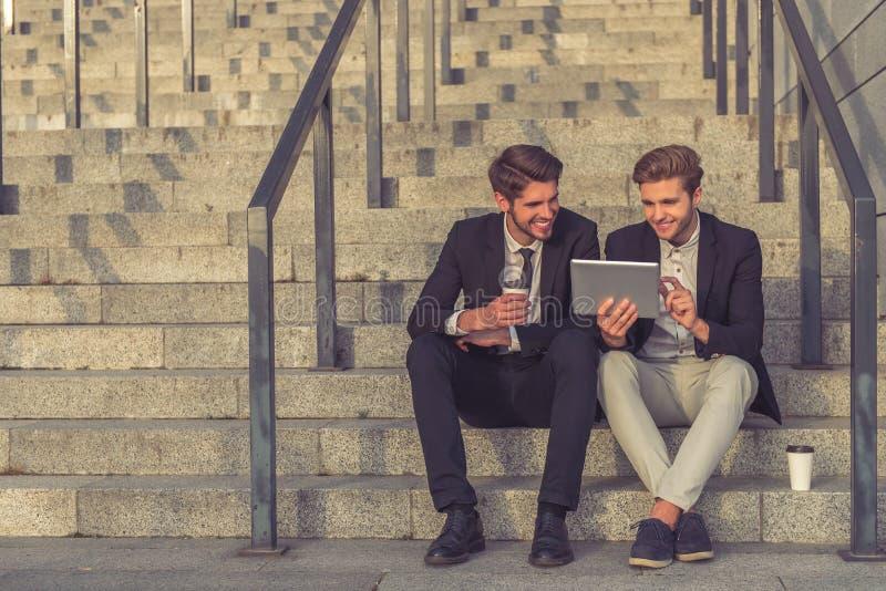 Homens de negócios novos consideráveis com dispositivo foto de stock