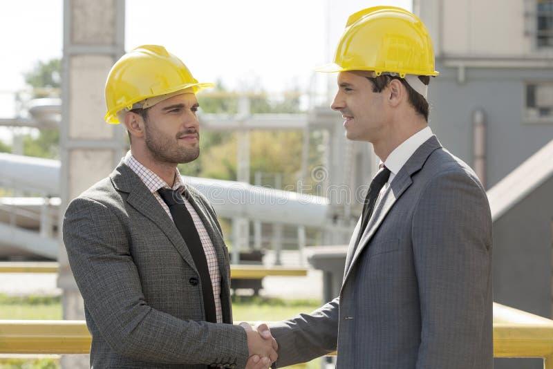 Homens de negócios novos nos capacetes de segurança que agitam as mãos no canteiro de obras foto de stock