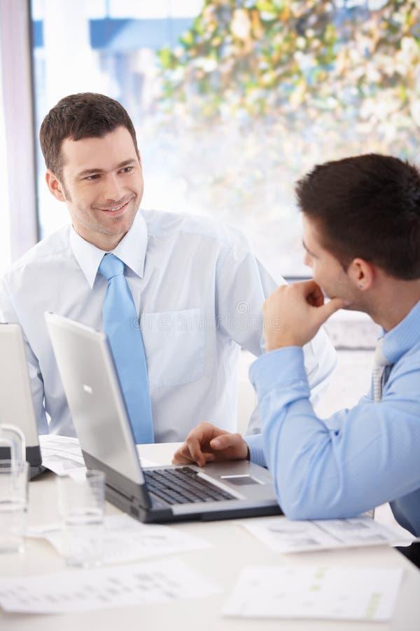 Homens de negócios novos que falam na tabela de reunião fotografia de stock royalty free