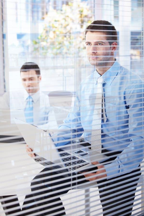 Homens de negócios novos que trabalham no escritório brilhante fotos de stock