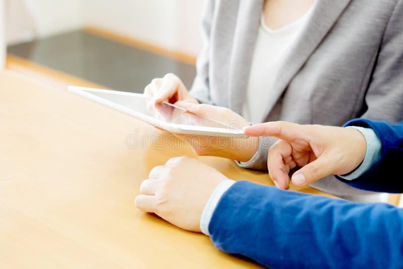 Homens de negócios novos que usam o Touchpad na reunião imagens de stock
