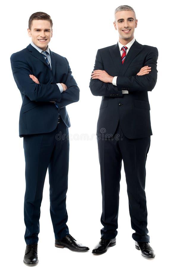 Homens de negócios novos seguros isolados no branco imagem de stock