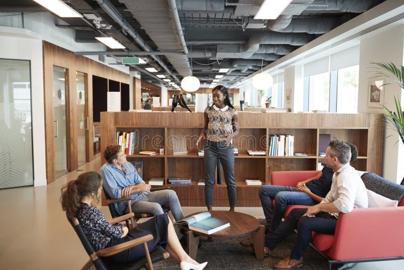 Homens de negócios ocasionalmente vestidos e mulheres de negócios que têm a reunião informal no escritório moderno imagem de stock royalty free