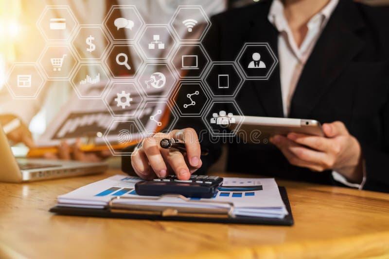 Homens de negócios ou analistas dos dados financeiros que trabalham com tabuletas e laptop e gráficos dos dados junto foto de stock