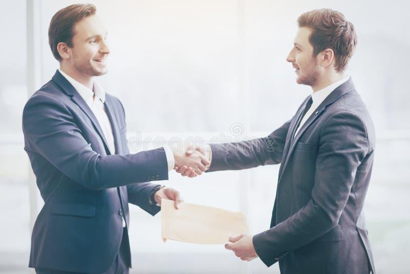 Homens de negócios que agitam as mãos com sorrisos amigáveis imagens de stock
