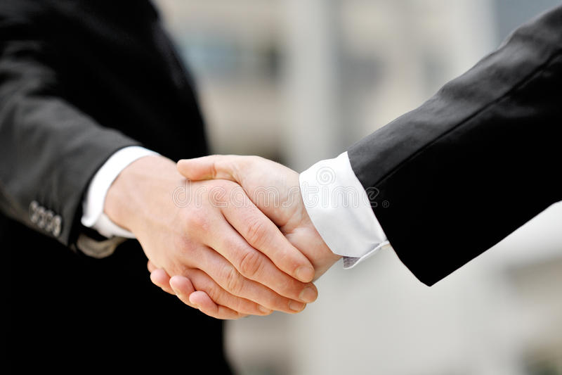 Homens de negócios que agitam as mãos - conceito da parceria do negócio de negócio fotografia de stock royalty free