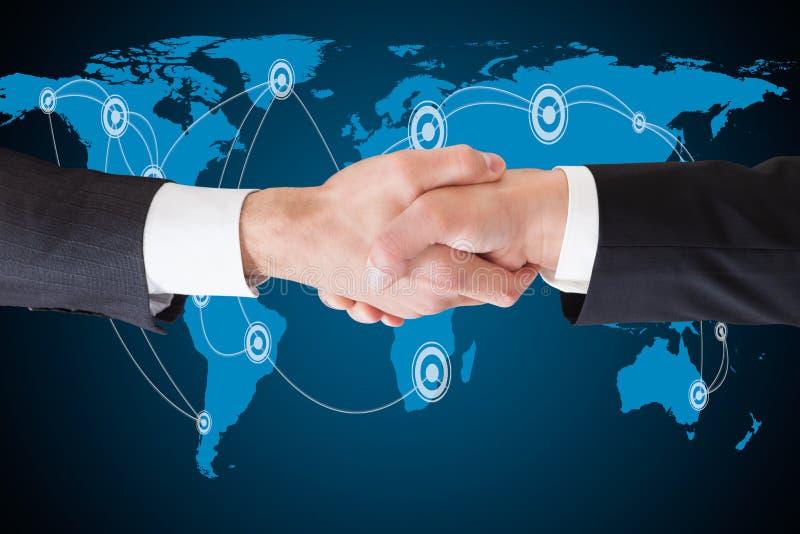 Homens de negócios que agitam as mãos contra o mapa do mundo foto de stock royalty free