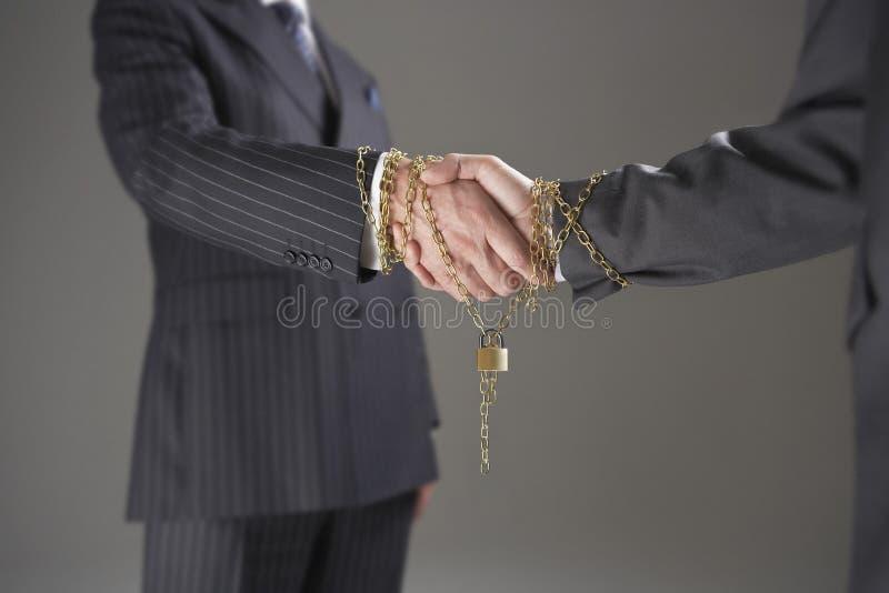 Homens de negócios que agitam as mãos envolvidas na corrente e no cadeado do ouro fotos de stock royalty free