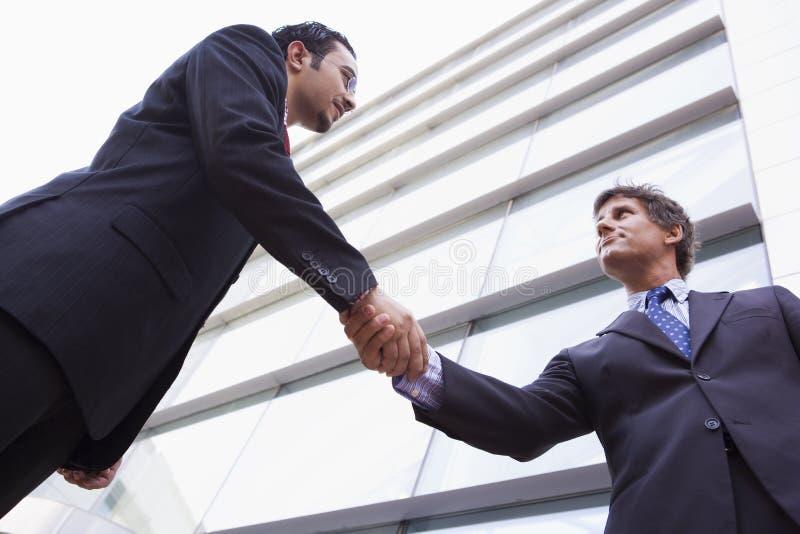 Homens de negócios que agitam as mãos fora do prédio de escritórios imagens de stock royalty free