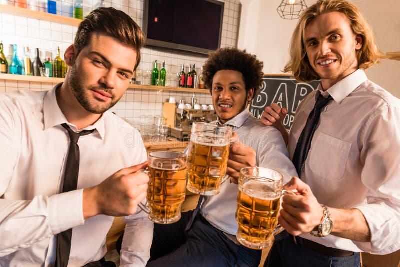 Homens de negócios que bebem a cerveja na barra foto de stock