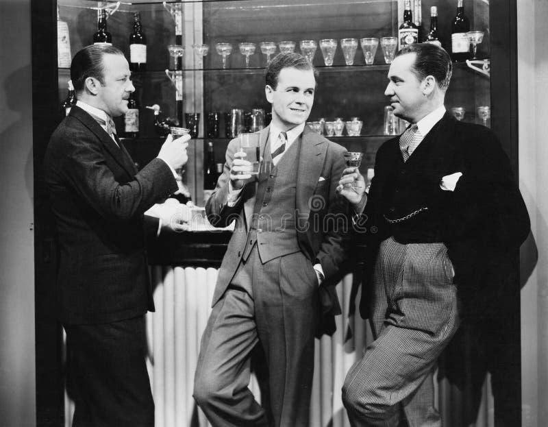 Homens de negócios que bebem junto na barra (todas as pessoas descritas não são umas vivas mais longo e nenhuma propriedade exist imagem de stock
