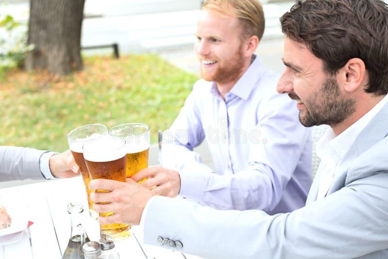 Homens de negócios que brindam vidros de cerveja com o colega fêmea no restaurante exterior foto de stock