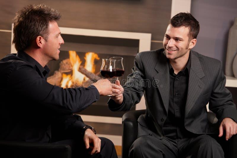 Homens de negócios que clinking vidros de vinho imagens de stock royalty free