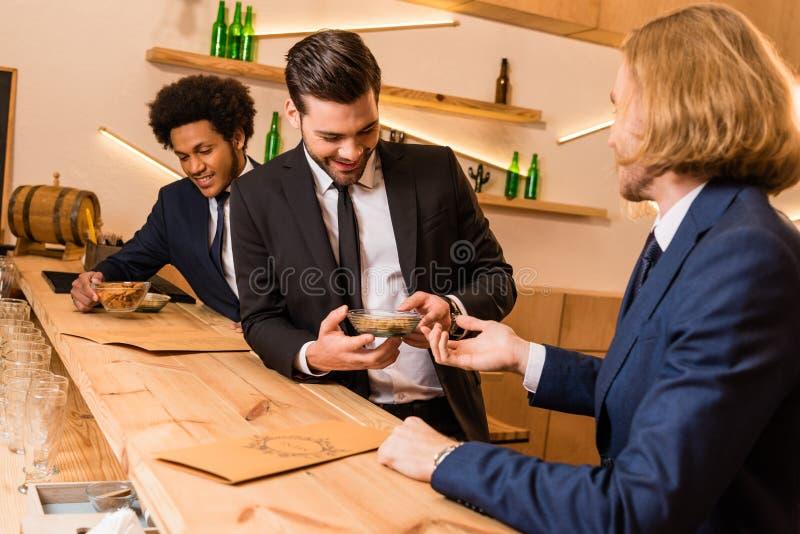 Homens de negócios que comem o petisco na barra fotografia de stock