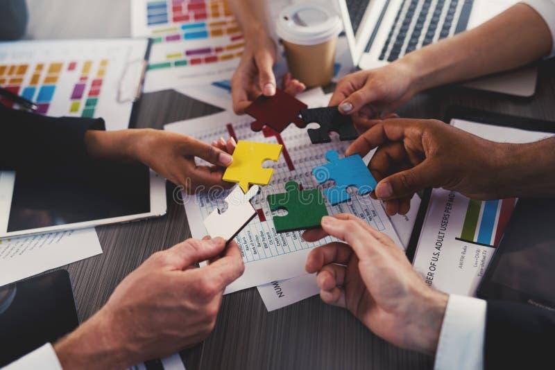 Homens de negócios que constroem enigmas coloridos junto Conceito dos trabalhos de equipa, da parceria, da integração e da partid fotografia de stock