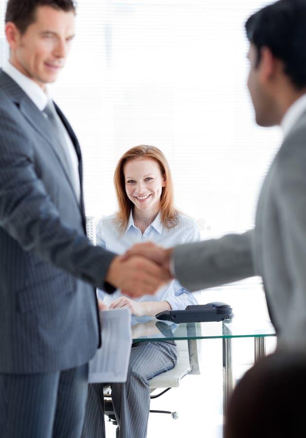 Homens de negócios que cumprimentam-se em uma entrevista de trabalho imagens de stock royalty free