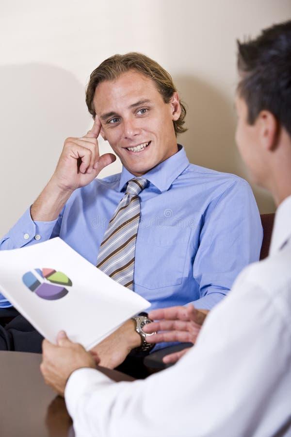Homens de negócios que discutem resultados financeiros foto de stock royalty free