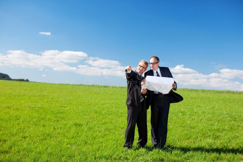 Homens de negócios que discutem um plano da construção fotografia de stock