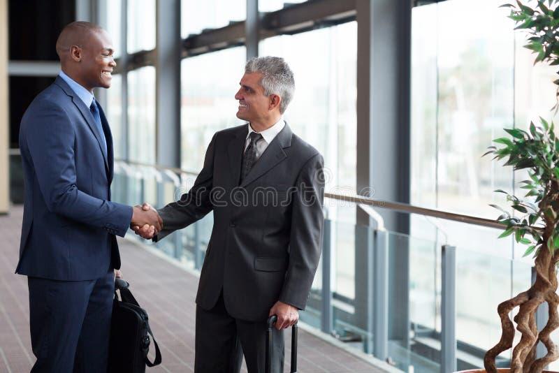 Homens de negócios que encontram o aeroporto imagem de stock royalty free