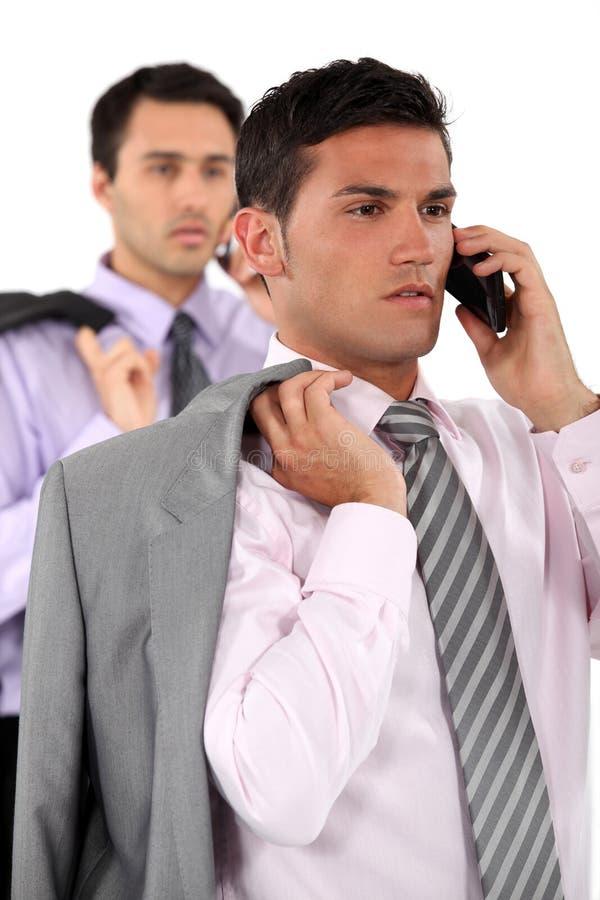 Homens de negócios que falam em seus móbeis fotografia de stock royalty free