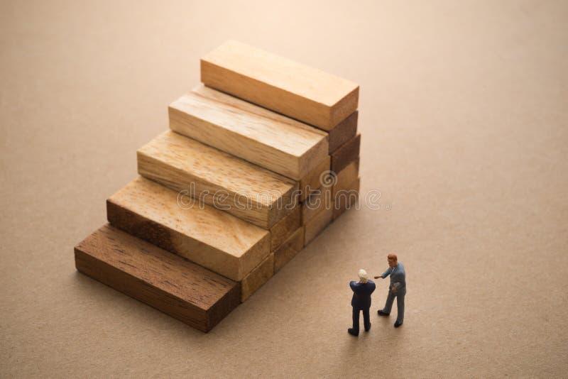 Homens de negócios que falam sobre a etapa do bloco de madeira imagens de stock