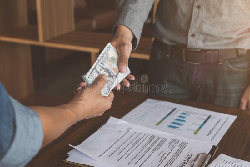 Homens de negócios que fazem o aperto de mão com dinheiro nas mãos, corrupção e fotos de stock