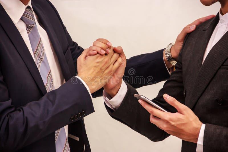 Homens de negócios que guardam a mão após o negócio confirmado no telefone esperto Ideia conceptual do sucesso, venda fechado, tr foto de stock