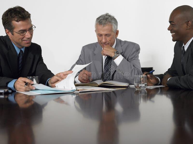 Homens de negócios que leem originais na sala de conferências imagens de stock royalty free