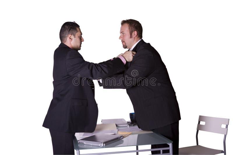 Homens de negócios que lutam através da mesa fotografia de stock